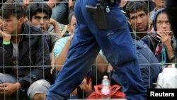 Беженцы за оградой в пункте приема мигрантов в Венгрии. Иллюстративное фото.