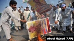 Members of a Pakistani trade union burn posters of U.S. President Donald Trump at a protest in Peshawar on August 30.
