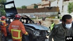 Volunteers search a badly damaged vehicle after a suicide bomb attack in Peshawar that killed three people on May 24.