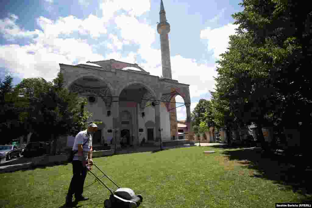 A man cuts the grass in the garden of the Grand Mosque in Kosovo's capital, Pristina.