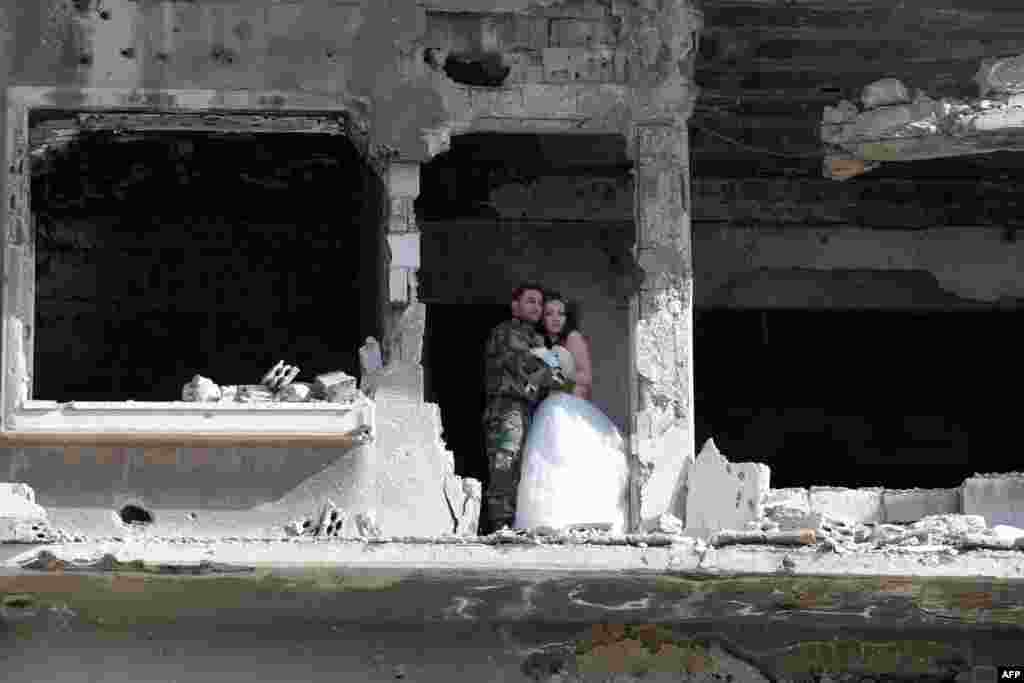 A newly-wed Syrian couple pose for a wedding picture amid heavily damaged buildings in the war-ravaged city of Homs. (AFP/Joseph Eid)
