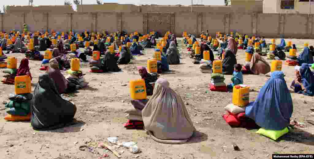 Afghans sit on the ground after they received ration aid in Kandahar. (efe-EPA/Muhammad Sadiq)