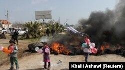 Djeca drže balone dok stoje kraj zapaljenih guma tokom prosvjeda protiv sporazuma o zajedničkim ruskim i turskim ophodnjama, na autocesti M4 u pokrajini Idlib, Sirija, 15. mart 2020.