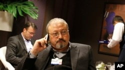 FILE - In this Jan. 29, 2011, file photo, Saudi Arabian journalist Jamal Khashoggi speaks on his cellphone at the World Economic Forum in Davos, Switzerland. The Washington Post said Wednesday, Oct. 3, 2018, it was concerned for the safety of Khashoggi, a