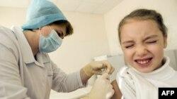 Дәрігер балаға вакцина салып жатыр. (Көрнекі сурет)