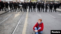 An antigovernment protester sits on the ground in front of police during a demonstration in Sarajevo.