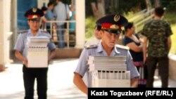 Полицейские несут материалы уголовных дел в зал заседания суда. Алматы, 13 июля 2011 года.