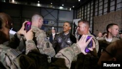 Soldiers take photos as U.S. President Barack Obama (center) shakes hands with troops after delivering remarks at Bagram Air Base near Kabul on May 25.
