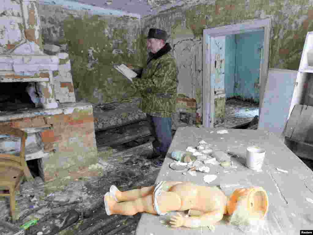 Makar Krosovski, 73, visits his abandoned and ruined house, which he left shortly after the Chornobyl blast, in the exclusion zone around the nuclear reactor. Photo by Vasily Fedosenko for Reuters