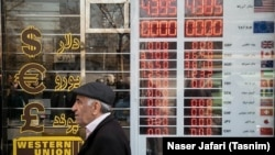 A man walks past a currency exchange shop in Tehran's business district on January 21, 2018.
