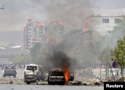A vehicle is seen on fire after a blast near the Afghan parliament