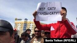 Участник протеста в Атырау держит плакат: «Продать землю — значит продать родину». 24 апреля 2016 года.