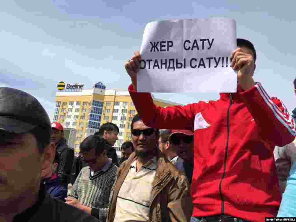 """Участник митинга держит плакат с надписью: """"Продать землю - значит продать родину""""."""