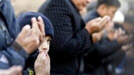 Люди молятся в центральной мечети Алматы.