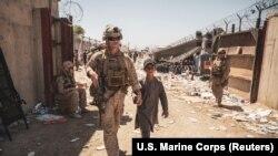 Морской пехотинец США сопровождает ребенка к семье во время эвакуации в аэропорту Кабула, 24 августа 2021 года