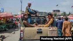 Боевики-талибы на пикапе передвигаются по рыночной площади. Кабул, 17 августа 2021 года