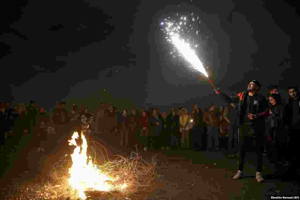 A man holds up a firework during Chaharshanbe Souri, or Wednesday Feast, an ancient Festival of Fire, on the eve of the last Wednesday of the solar Persian year, in Tehran, Iran, Tuesday, March 19, 2019.
