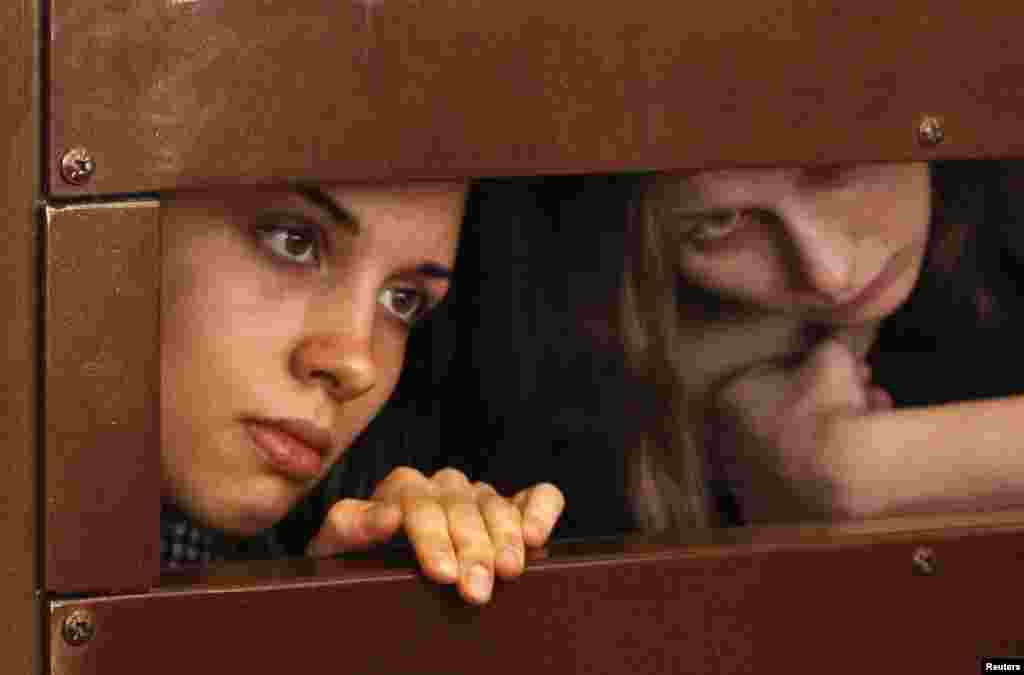 Nadezhda Tolokonnikova (left) and Maria Alyokhina look out from the defendant's cell in a Moscow courtroom on July 30.