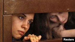 "Nadezhda Tolokonnikova (left) and Maria Alyokhina, members of female punk band ""Pussy Riot,"" look out from the defendant's cell in a courtroom in Moscow on July 30."