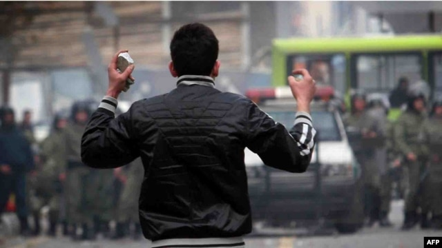 A protester holds stones as he faces off against security forces in Tehran in December 2009