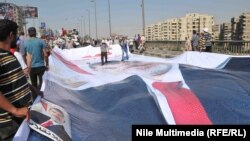موالون لجماعة الإخوان المسلمين يهيؤون صورة كبيرة للرئيس المعزول محمد مرسي