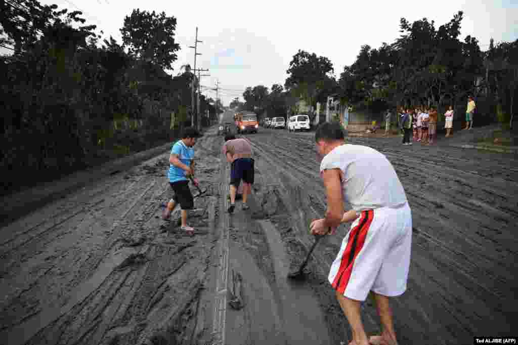 Meštani čiste ceste nakon što je pepeo prekrio grad Tanauan, južno od Manile