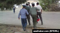 Polisiýa işgärleri bir adamy soraga äkidip barýarlar.