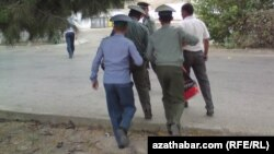 Türkmen howpsuzlyk gulluklary bir adamy soraga äkidip barýarlar. Arhiwden