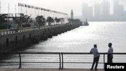 Мужчины на мосту в китайском портовом городе Циндао.