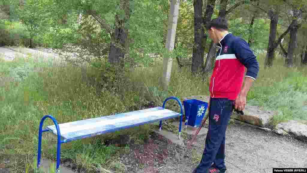 Мужчина, принявший участие в благоустройстве паркового озера, осматривает только что установленные лавочки и урны, которые для надежности забетонировали.