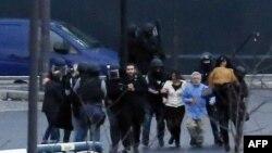Спецпризначенці виводять врятованих заручників із крамниці під час штурму, 9 січня 2015 року