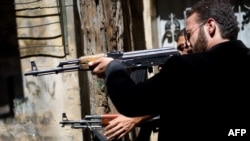 Members of the Free Syrian Army shoot at a nearby government army position in the Al-Jadeida neighbourhood of Aleppo.