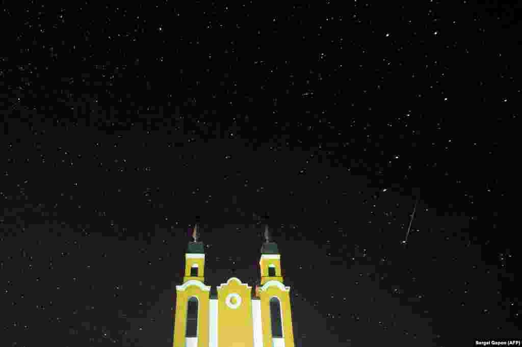 A meteor streaks across the sky behind a Catholic church during the annual Geminid meteor shower in the village of Krevo, some 100 kilometers northwest of Minsk. (AFP/Sergei Gapon)