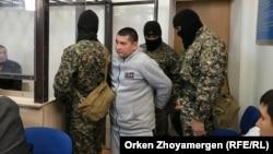 Вооруженный конвой заводит в зал подсудимого Аманжола Жансенгирова. Нур-Султан, 22 октября 2019 года.