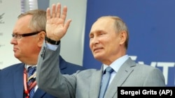 Russian President Vladimir Putin waves to the crowd at the Russian Formula One Grand Prix in Sochi on September 30.