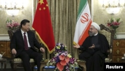 Iranian President Hassan Rouhani (R) meets with Chinese President Xi Jinping in Tehran on January 23,