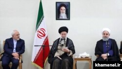 A handout picture provided by the office of Iran's Supreme Leader Ayatollah Ali Khamenei on July 15, 2018 shows Khamenei (C) sitting between President Hassan Rouhani (R) and Foreign Minister Mohammad Javad Zarif (L) during a government meeting in the capi