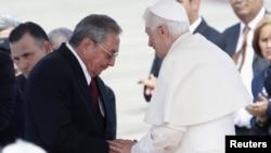 Кубинский президент Рауль Кастро привествует Бенедикта XVI в аэропорту Сантьяго-де-Куба 26 марта 2012 года.