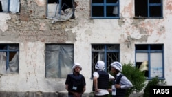 OSCE observers inspect buildings damaged during shelling in the Donetsk region earlier this week. A recent uptick in violence in the area saw a patrol from the OSCE Special Monitoring Mission shot at on May 27