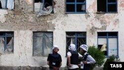 Vëzhguesit e OSBE-së duke e shikuar një ndërtesë të dëmtuar nga sulmet me predha në rajonin Donjeck më 26 maj
