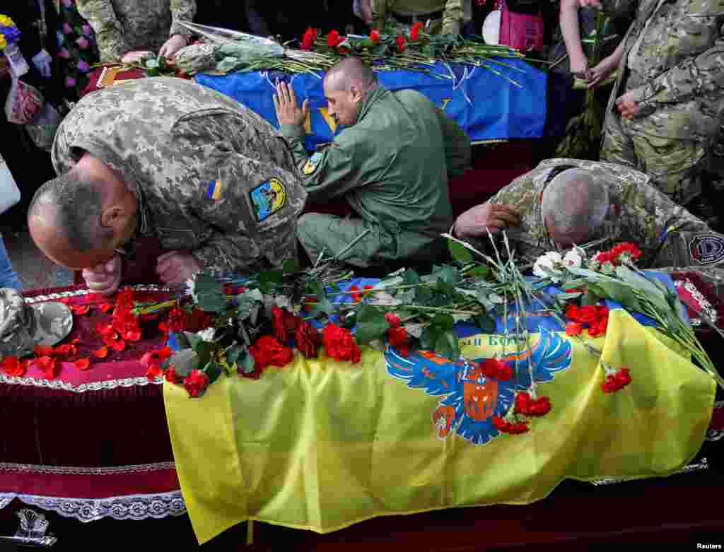 Fighters take part in a funeral ceremony for Mykola Kuliba and Serhiy Baula, from the volunteer Aydar battalion, who were killed in fighting in eastern Ukraine, on Independence Square in central Kyiv. The battalion has been accused of committing war crimes by Amnesty International. (Reuters/Gleb Garanich)