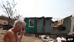 A man stands near the charred remains of his burned-out home in Voronezh on August 3.