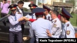 Police take away a protester in the Almaty district of Duman.