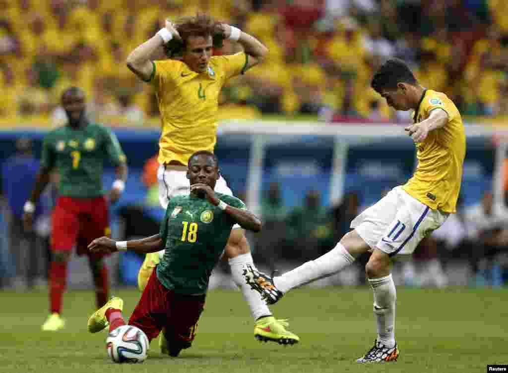 Бразилиялық ойыншылар Оскар (оң жақта) мен Давид Лиус қыспаққа алған Камерун құрамасының жартылай қорғаушысы Эйонг Эно допқа жете алмай сүрініп кетті.