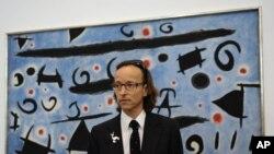 """Внукът на Миро - Жоан Пуниет Миро позира пред картината на своя дядо """"Хора и птици танцуват на синьо небе; Искри"""""""