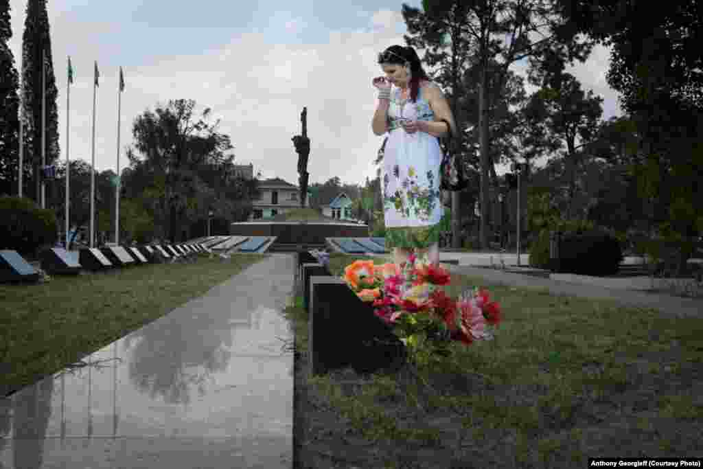 A woman lays flowers at the grave of a relative killed in the 1992-1993 war. A square in central Sukhumi has been turned into a large cemetery.