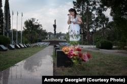 Мемориал в центре Сухуми. Женщина на могиле родственников, убитых в 1992 году