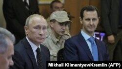 Ресей президенті Владимир Путин мен Сирия президенті Башар Асад (оң жақта) Латакия провинциясындағы Хмеймим әуе базасында. Желтоқсан, 2017 жыл.