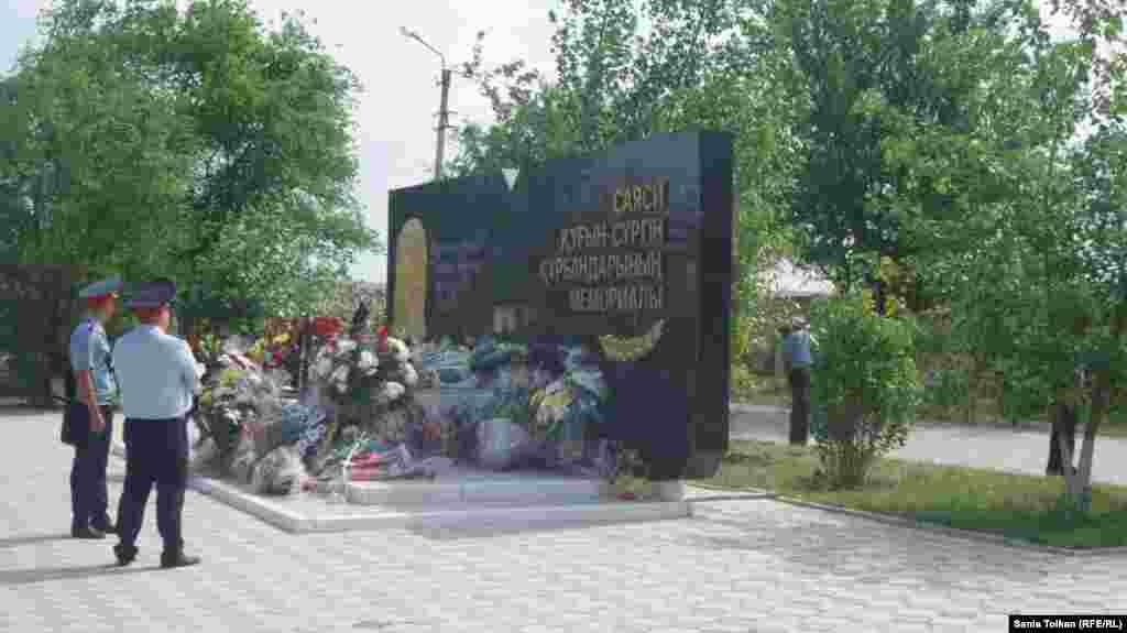 Мемориал маңын бақылап жүрген полиция қызметкерлері жұрт қойып кеткен гүлдерге қарап тұр. Атырау, 31 мамыр 2016 жыл.