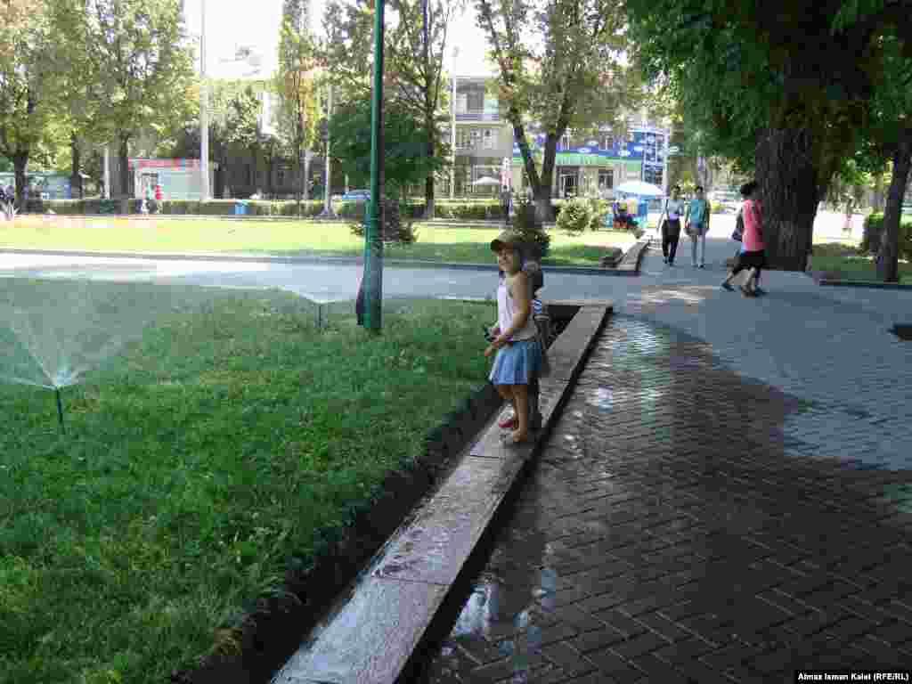 Летний Бишкек - Детвора с восторгом и визгом купается в брызгах воды от поливальных фонтанчиков.
